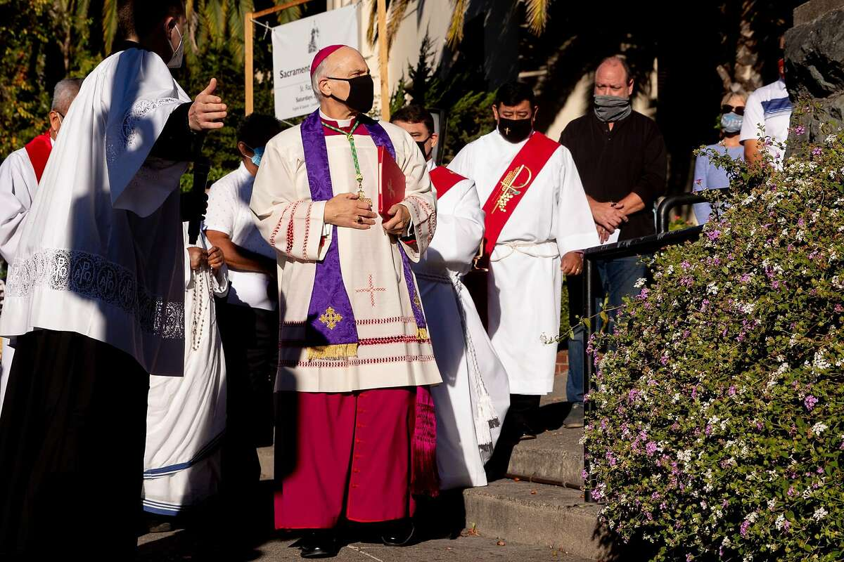 San Francisco's Archbishop Salvatore Joseph Cordileone (second left) arrives to conduct an exorcism outside of Church of Saint Raphael in San Rafael, Calif. Saturday, October 17, 2020 on the spot where a statue of St. Junipero Serra was toppled during a protest October 12.