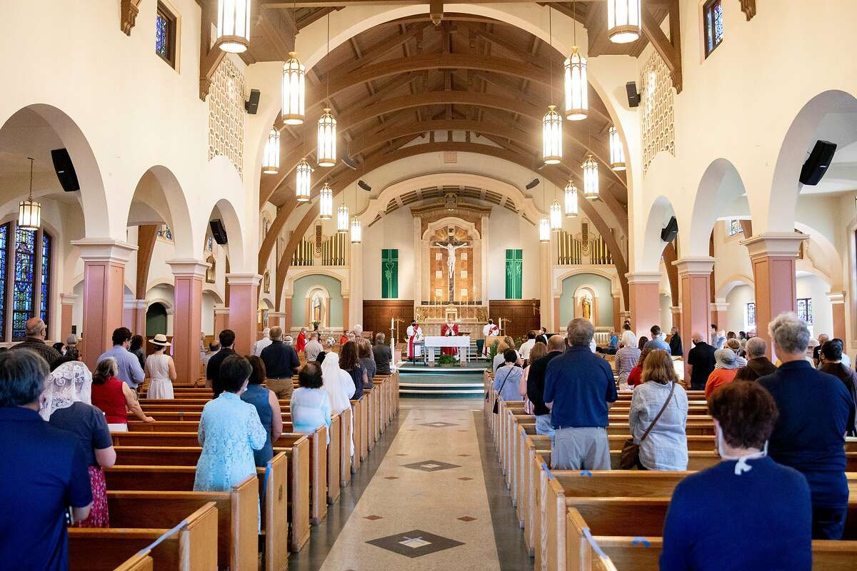 Worshipers stand socially distanced with masks on during an indoor Mass at St. Raphael Catholic Church in San Rafael.
