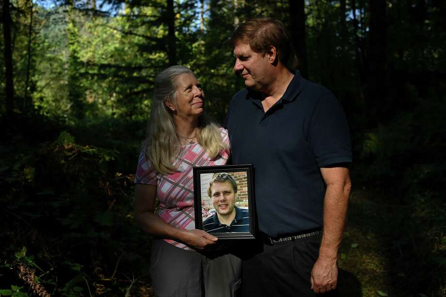 """Barbara Kenny and her husband, Chris Kenny, hold a photo of their child Stacy """"Patrick"""" Kenny. Kenny, who suffered from schizophrenia, was killed by Springfield, Ore., police Sgt. Richard A. Lewis in 2019 during a traffic stop. Photo: Washington Post Photo By Joshua Lott. / The Washington Post"""