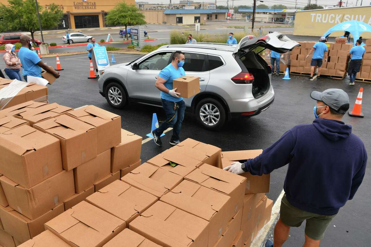 Roger Gonzalez loads a vehicle as Keith Turgeon (right) gets ready for the next vehicle during a drive through food distribution event Saturday morning for residents impacted by the Coronavirus. AT&T volunteers hoped to distibute 500 bags fiolled with rice, beans, potatoes, and fresh produce at the AT&T store at 2639 NW Loop 410.