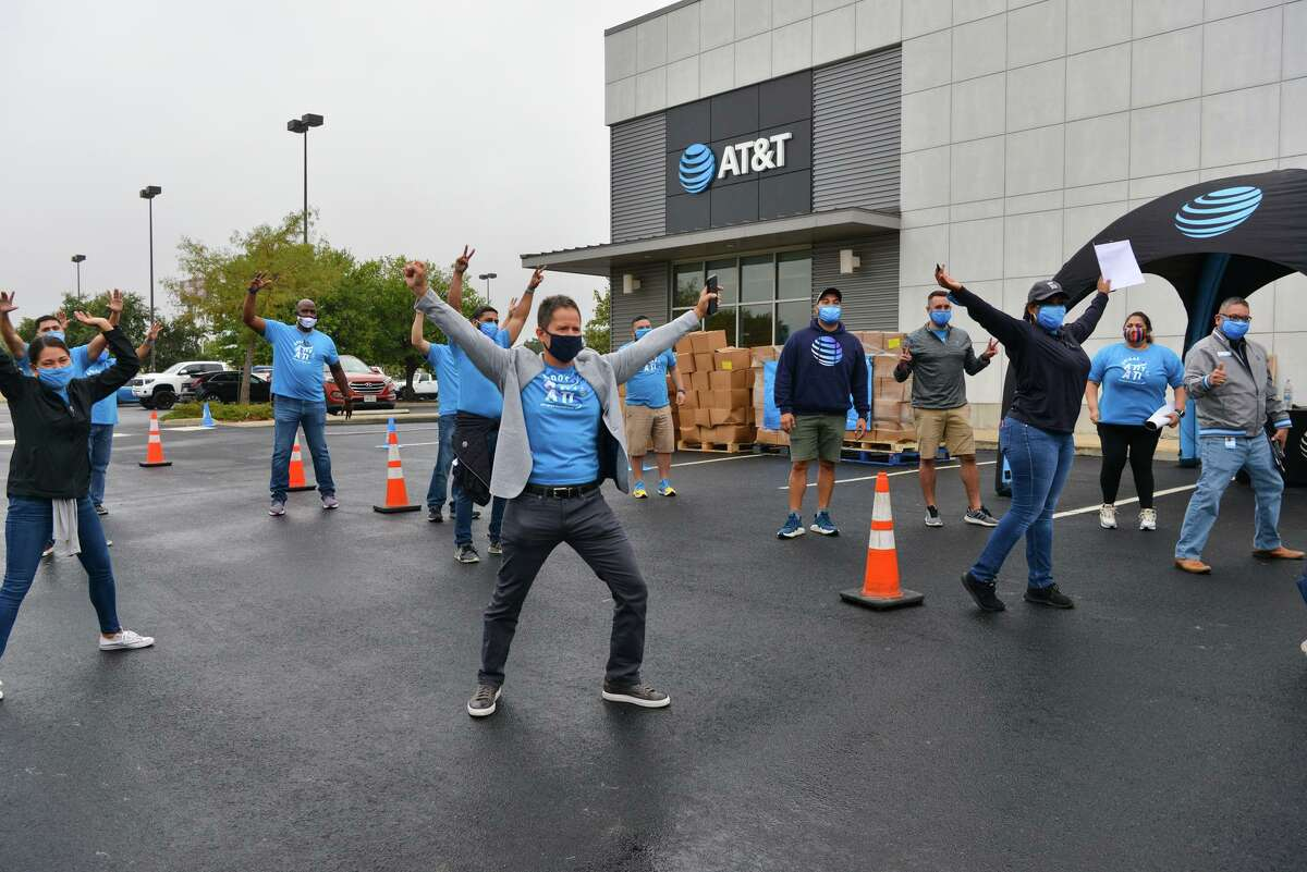 Volunteers do a group dance before a drive through food distribution event Saturday morning for residents impacted by the Coronavirus. AT&T volunteers hoped to distibute 500 bags fiolled with rice, beans, potatoes, and fresh produce at the AT&T store at 2639 NW Loop 410.