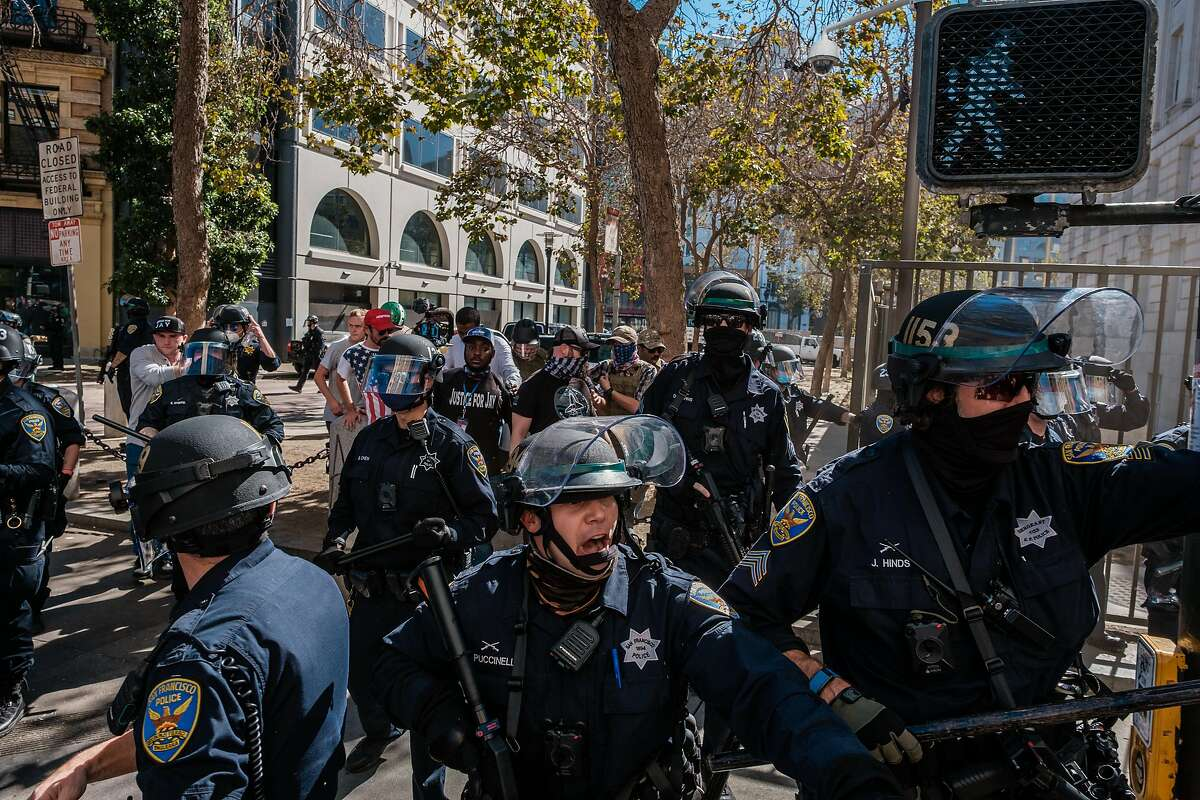 Police push counterprotesters back as they try to escort supporters of President Trump from a free speech rally and protest in San Francisco on Saturday.