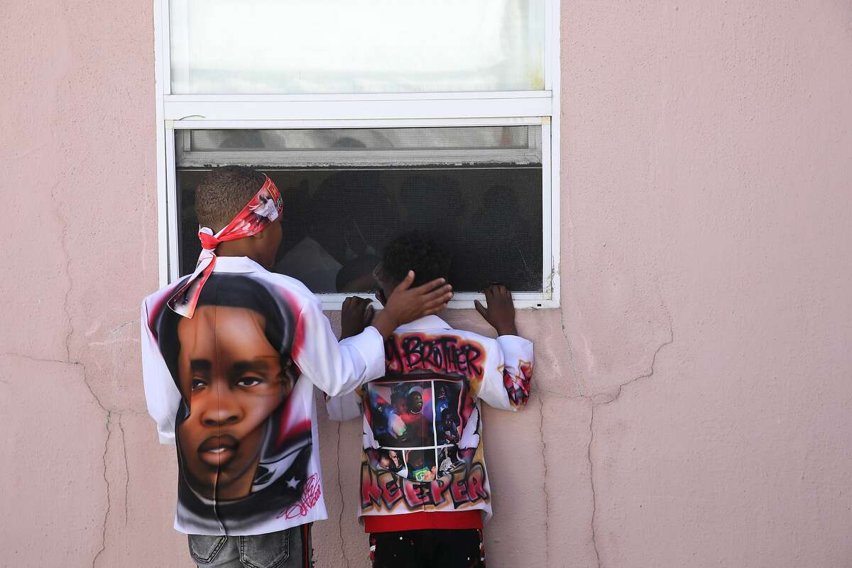 Trayvon Hall, 7, left, comforts his cousin, Kai Pryor, 4, as he peeks through a window during the funeral service of his older brother Aaron Pryor.