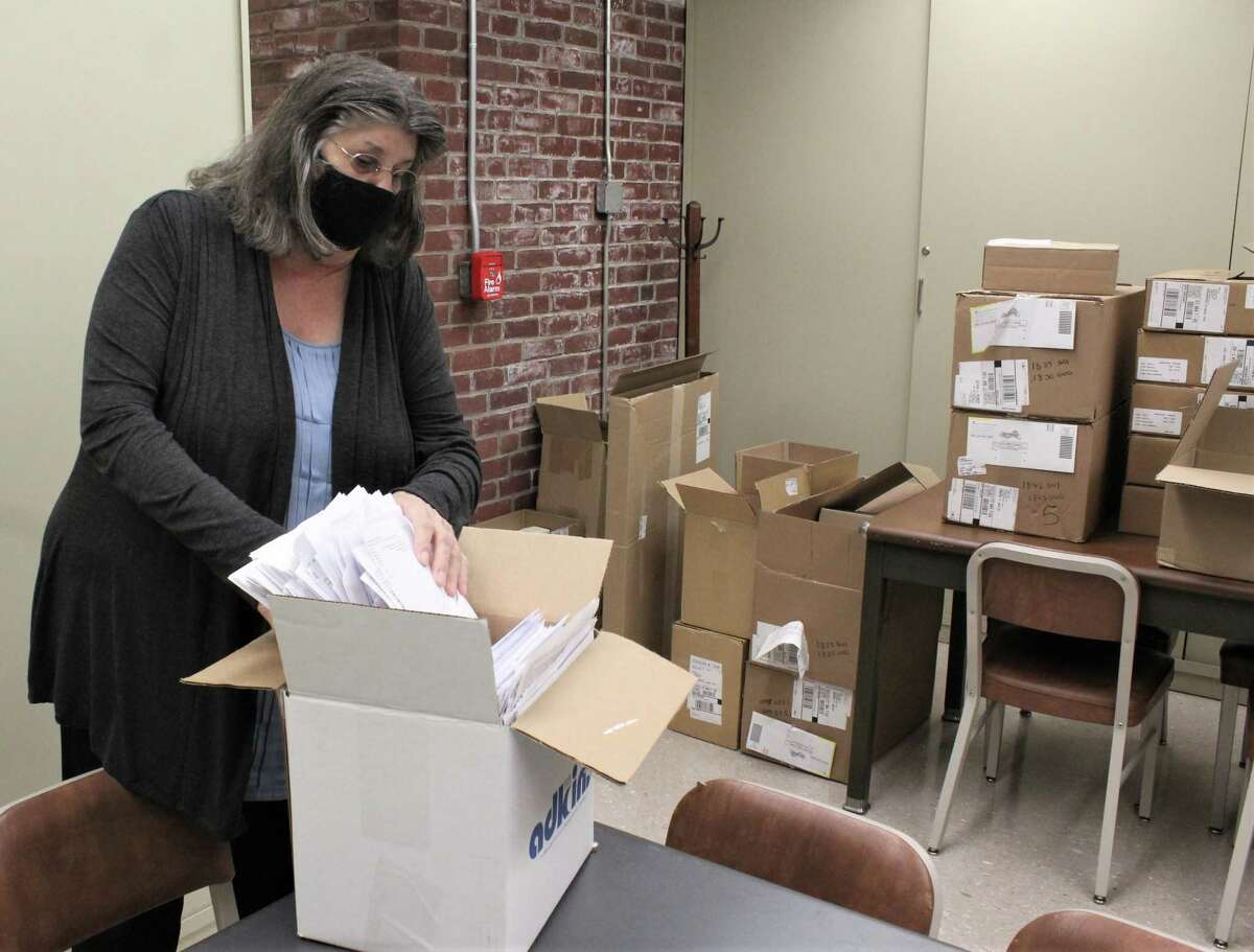 At Woodbridge town hall, Town Clerk Stephanie Ciarlegio works to prepare ballots in a room with materials provided by the state. She's shown with Alexis Bernstein, a temporary employee sorting ballots in the vault room. Also pictured is the drop-off ballot box in front of the building.
