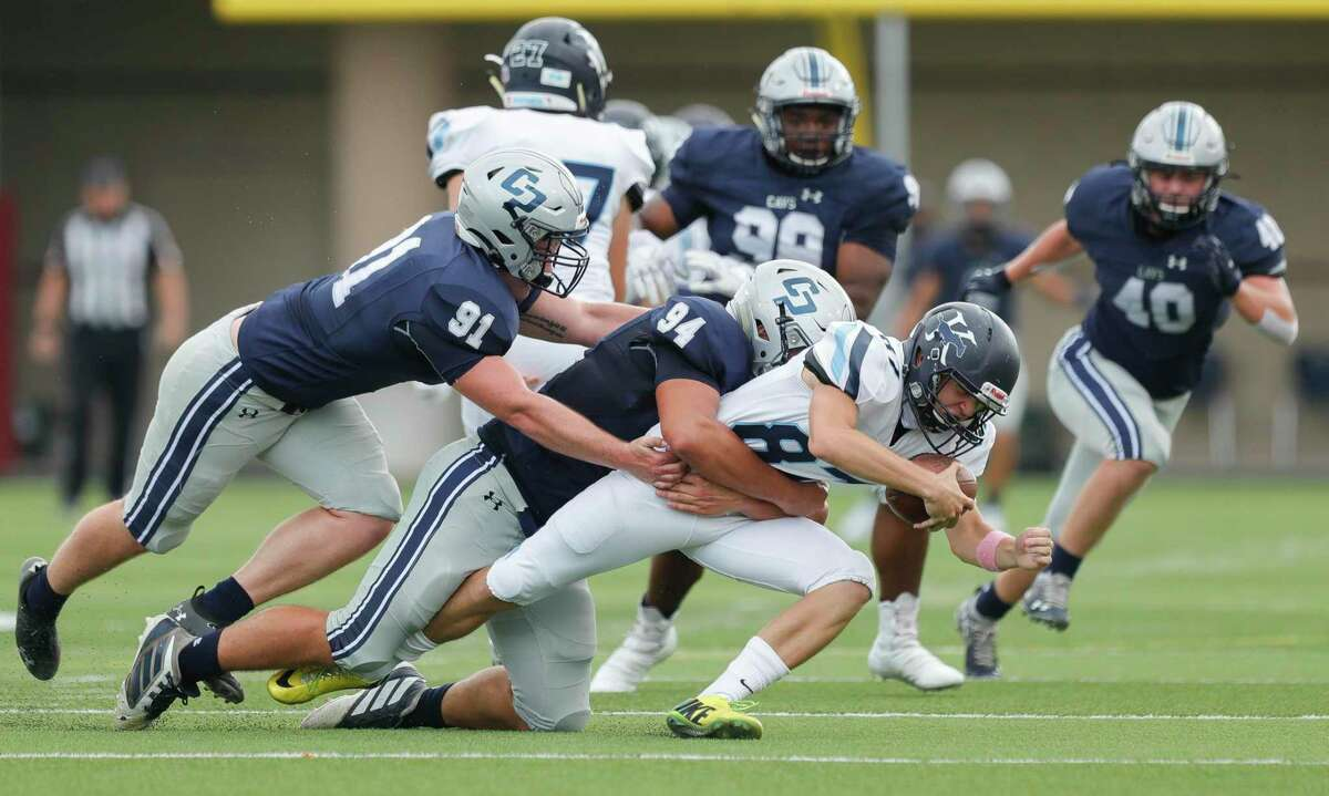 College Park defensive linemen Andrew Edmonson (94) and Grant Ferguson (91) tackle Kingwood kicker Kaden Wooster (87) after he fumbled the punt during the first quarter of a non-district high school football game at Woodforest Bank Stadium, Saturday, Oct. 17, 2020, in Shenandoah.