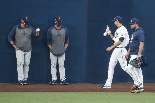 Houston Astros pitching coach Brent Strom, far left, standing with Josh Miller, waves a baseball at Tampa Bay Rays Charlie Morton as the Rays starter walks to the bullpen before Game 7 of the American League Championship Series at Petco Park Saturday, Oct. 17, 2020, in San Diego. Photo: Karen Warren/Staff Photographer / © 2020 Houston Chronicle