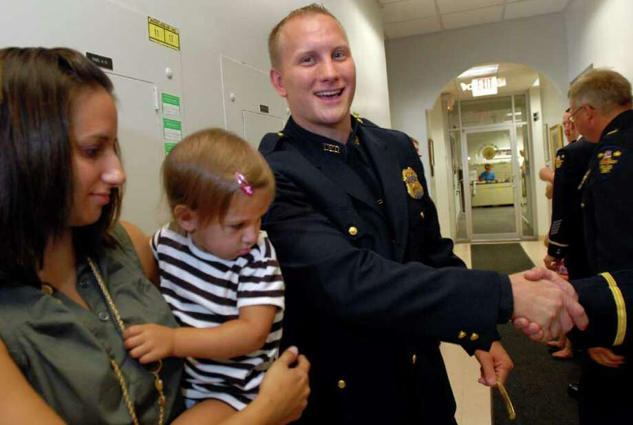 Troy Police Sgt. John F. Keeler receives congratulations during a ceremony to promote him and Capt. Terry Buchanan (not pictured) on Tuesday, Aug. 31, 2010, at City Hall in Troy. Joining Keeler are his wife, Jessica, and 1-year-old daughter, Tessa. (Cindy Schultz / Times Union) Photo: Cindy Schultz / 00010042A