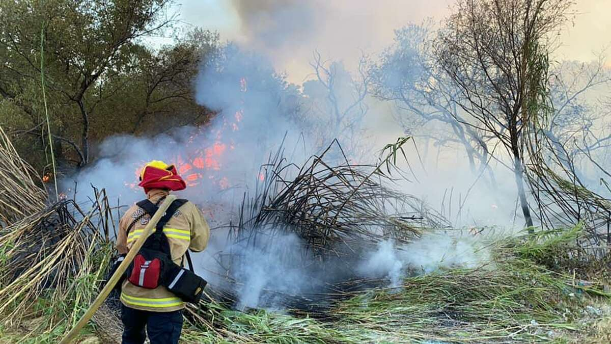 Firefighters were responding to a blaze that prompted evacuations and was threatening homes in Vacaville Saturday afternoon. In this photo, taken by Vacaville Fire Department, firefighters work to contain the brush fire between Vine Street and Markham Avenue.