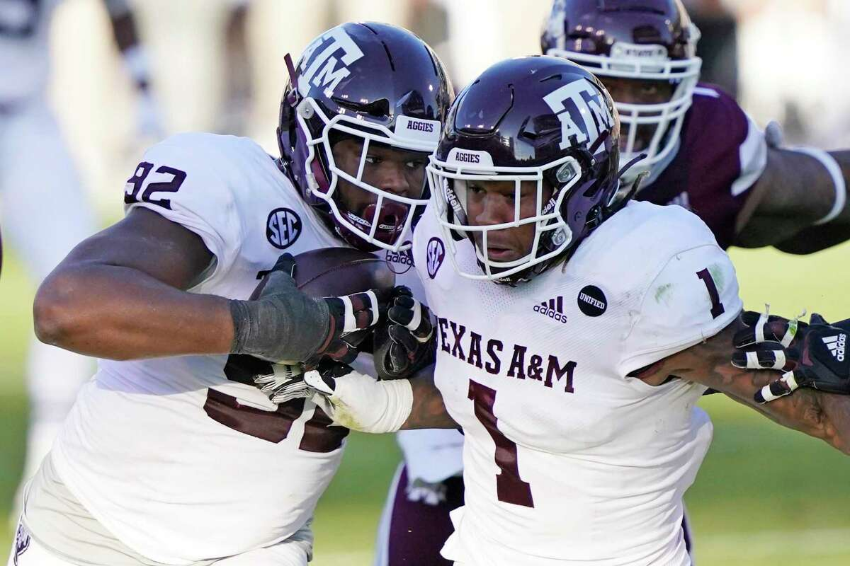 Texas A&M's Jayden Peevy, left, is escorted downfield by Buddy Johnson after Peevy's second-half fumble recovery.