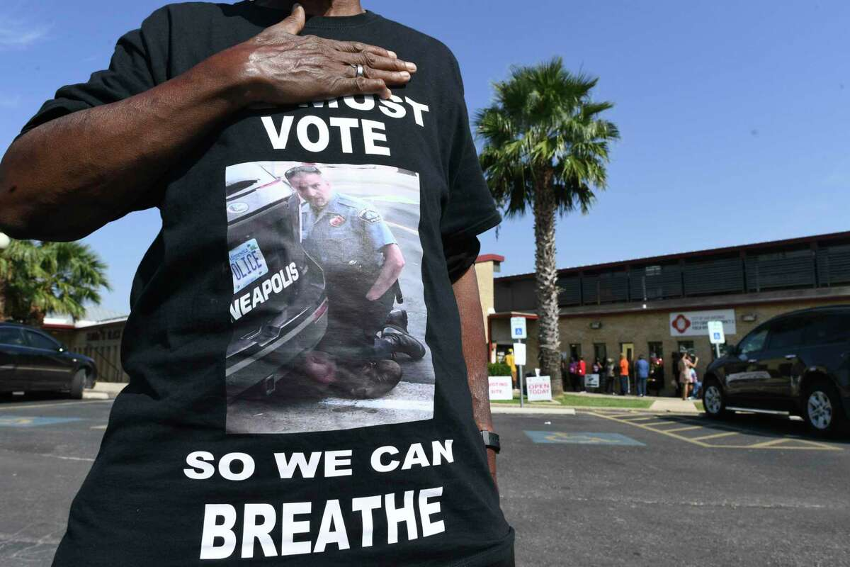 """Madeline Lee wears a shirt bearing a picture of the death of George Floyd at the hands of a Minnesota police officer """"to get the young people's attention to let them understand how it is important for us to vote"""" at the Claude Black Community Center on Tuesday, Oct. 13, 2020, the first day of early voting."""