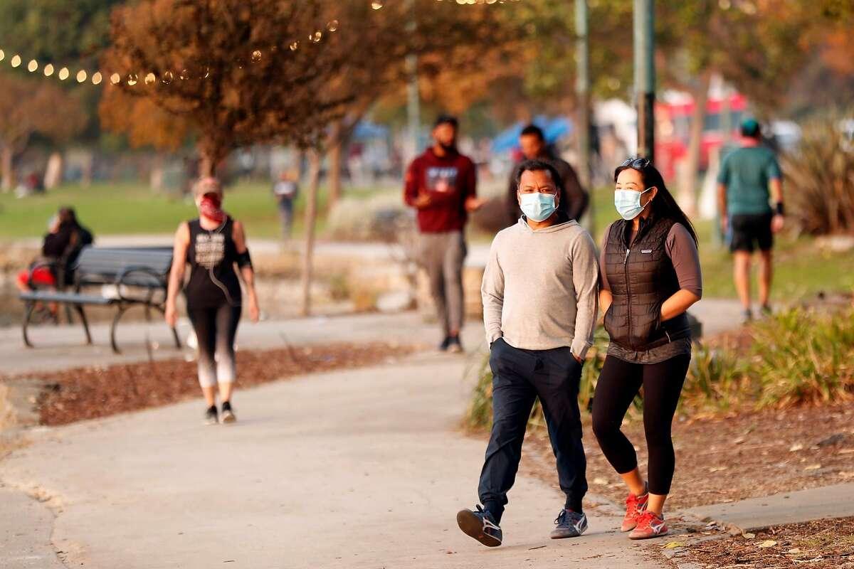 People walk along Lake Merritt in Oakland, October 8, 2020.