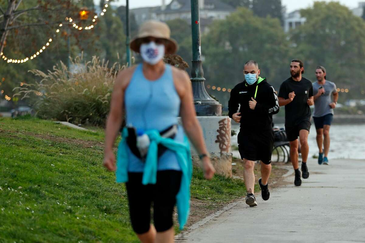 Joggers with and without face coverings exercise at Lake Merritt in Oakland. Most Bay Area counties are opting for education about masks rather than fines.