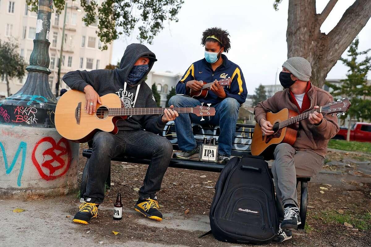 Roommates Sam Fletcher (left), Jeremy Neal and Jesse Rosenthal jam at Lake Merritt.