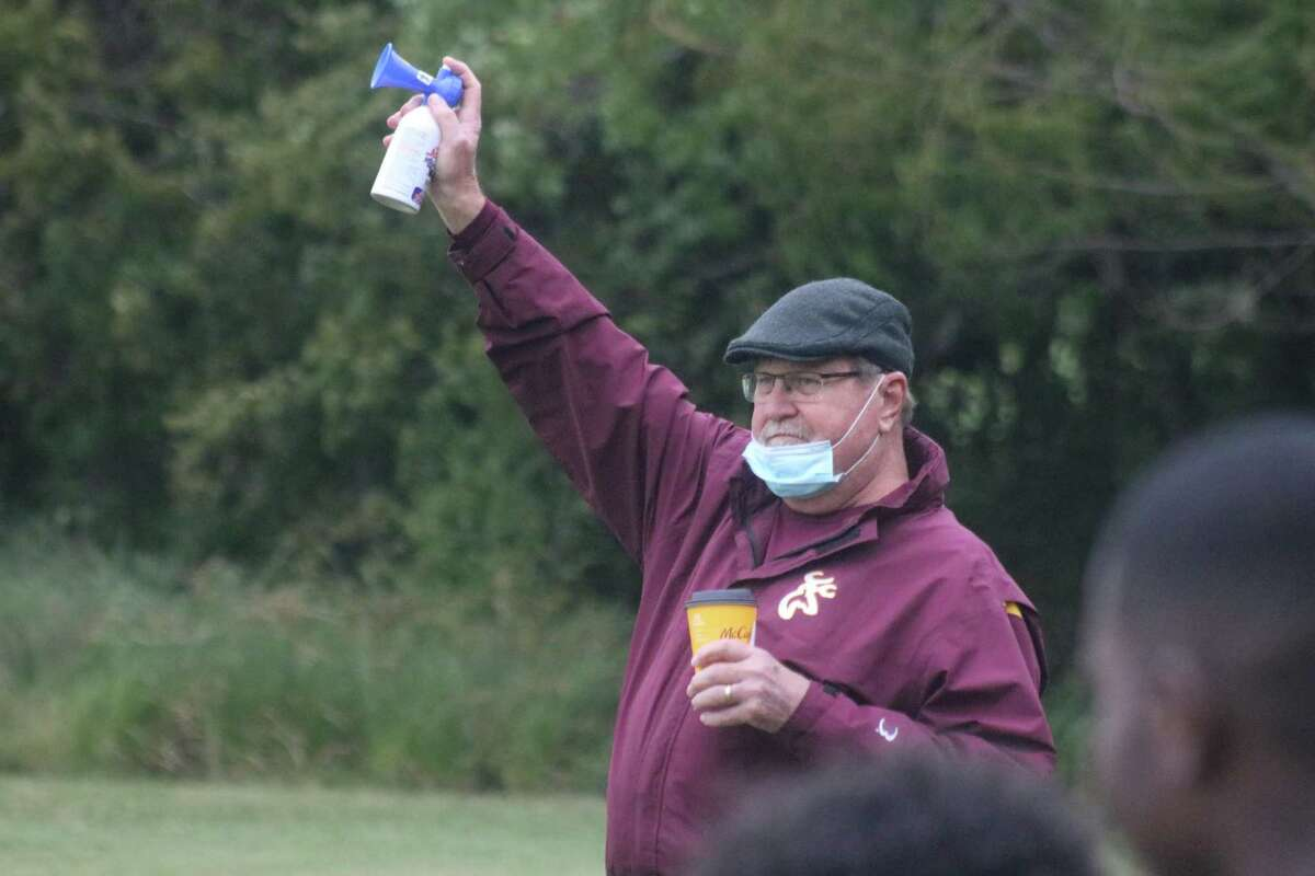 Official starter Russell Elfstrom prepares to sound the air horn for another race at the chilly Deer Park Invitational Friday morning.