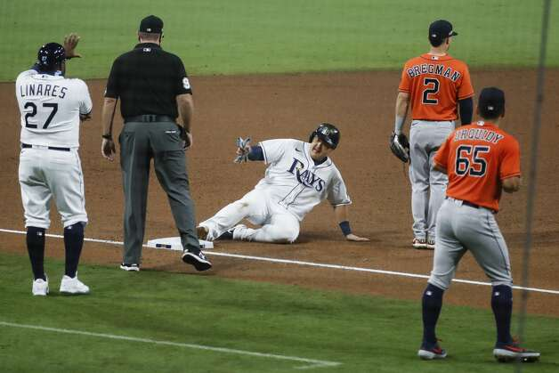 Tampa Bay Rays Ji-Man Choi slides safely into third past Houston Astros Alex Bregman (2) as he advanced on a sacrifice fly by Mike Zunino during the sixth inning of Game 7 of the American League Championship Series at Petco Park Saturday, Oct. 17, 2020, in San Diego. Photo: Karen Warren/Staff Photographer / © 2020 Houston Chronicle