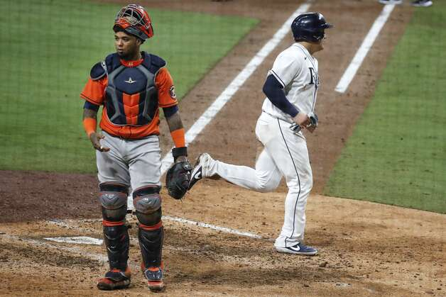 Tampa Bay Rays Ji-Man Choi jogs past Houston Astros Martin Maldonado as she scored on a sacrifice fly by Mike Zunino during the sixth inning of Game 7 of the American League Championship Series at Petco Park Saturday, Oct. 17, 2020, in San Diego. Photo: Karen Warren/Staff Photographer / © 2020 Houston Chronicle