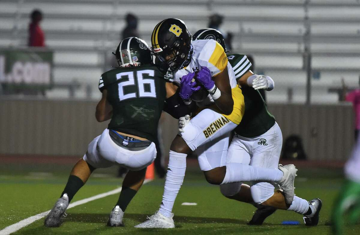 Brennan's Jalen Spells goes through Reagan's Giuseppe Sessi (26) and Bryce Hamilton on the way to the first of two first quarter touchdowns during their game Saturday night at Commalander Stadium