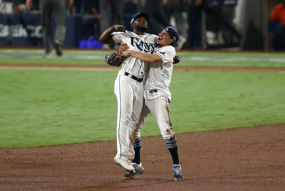Above, Randy Arozarena (left) and Willy Adames of the Rays hug after defeating the Astros 4-2 in Game 7 of the ALCS. Below, Rays starter Charlie Morton was lifted after just 66 pitches. Photo: Ezra Shaw / Getty Images