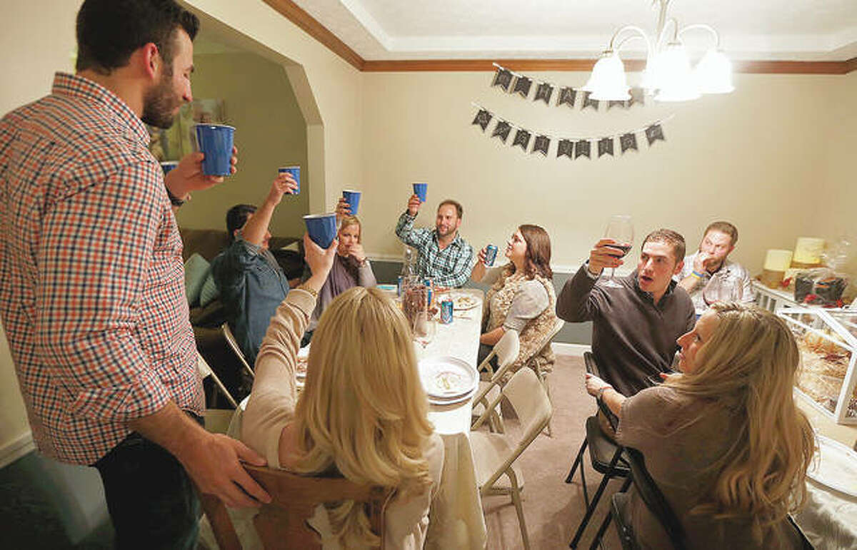 Friends share a toast during Mallory and Kevin Peters' annual Friendsgiving gathering in 2014. As the holidays approach, the pandemic is forcing people to come up with creative ways to celebrate.
