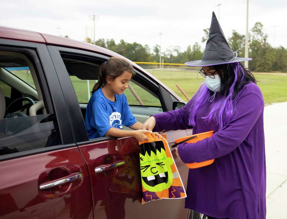 Anethe Farias, right, passes out candy during an annual Halloween event hosted by the Conroe Parks and Recreation department on Saturday at Carl Barton, Jr. Park. Visitors were invited to dress up in costume as they stopped by 22 different stations for treats. Photo: Gustavo Huerta, Houston Chronicle / Staff Photographer / 2020 © Houston Chronicle
