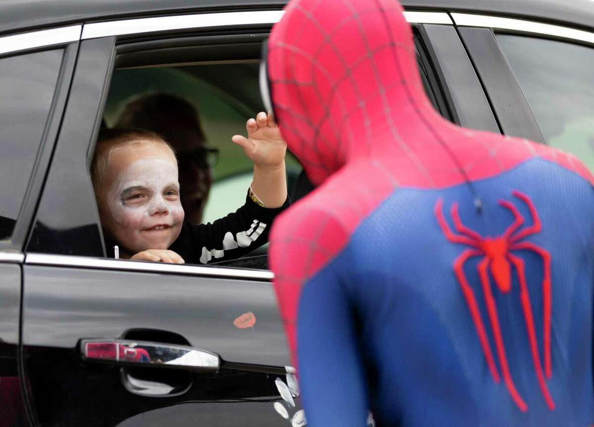 A child waves at Spiderman during an annual Halloween event hosted by the Conroe Parks and Recreation department, Saturday, Oct. 17, 2020, at Carl Barton, Jr. Park. Visitors were invited to dress up in costume as they stopped by 22 different stations for treats.