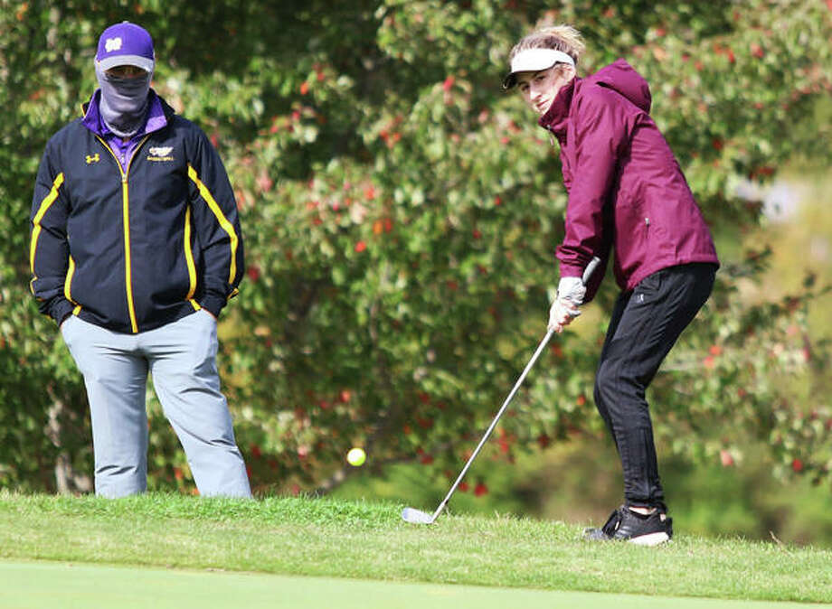 CM senior Meredith Flack (right), with Eagles coach Josh LeMond looking on, chips onto the green on hole No. 7 at Salem Country Club last Monday in the Salem Class 1A Sectional. Flack shot a career-low 93 in her final match for the Eagles. Photo: Greg Shashack | The Telegraph