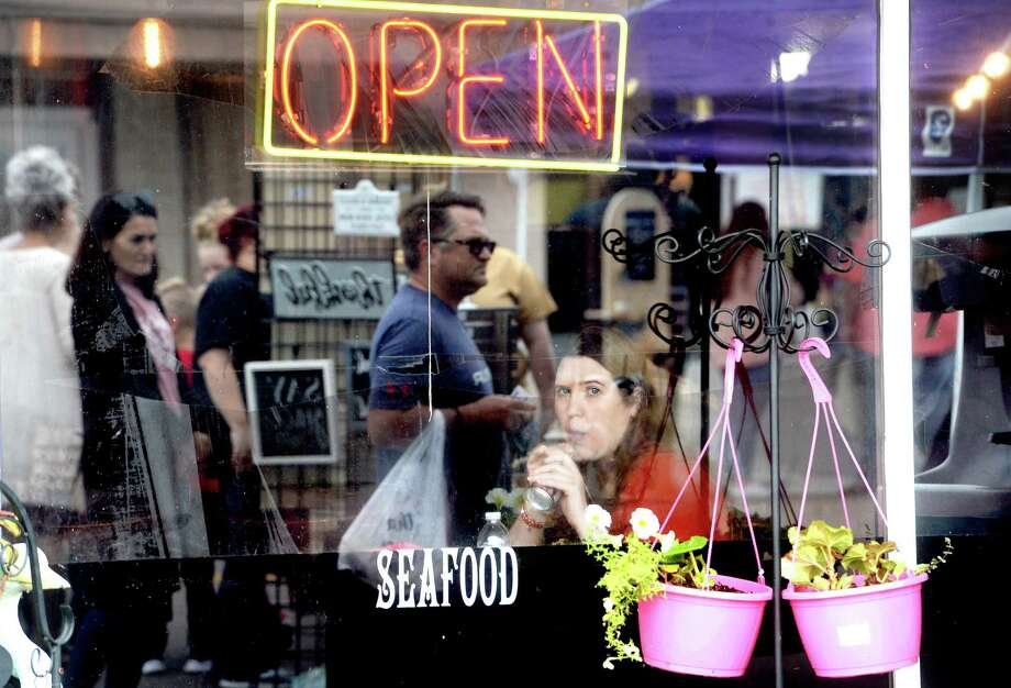 Therese Markham watches the stream of shoppers along Boston Avenue from her window seat while lunching at Touch of Cajun Cafe during Nederland's Fall Fest Saturday. Photo taken Saturday, October 17, 2020 Kim Brent/The Enterprise Photo: Kim Brent / The Enterprise / BEN