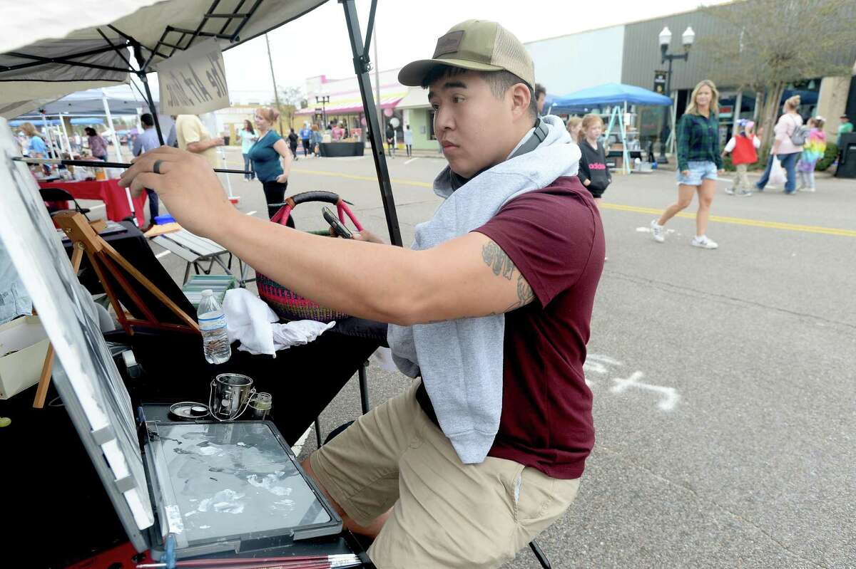 Artist Peter Nguyen paints a portrait while helping at The Art Studio, Inc., booth as shoppers fill Boston Avenue, perusing the vendor booths and open shops during Nederland's Fall Fest Saturday. Photo taken Saturday, October 17, 2020 Kim Brent/The Enterprise