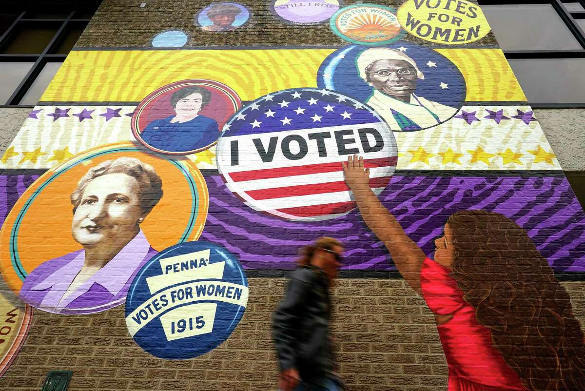 A pedestrian passes a mural celebrating women's voting rights in Erie.