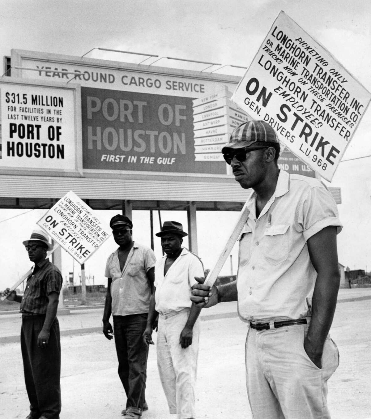 Teamster pickets who halted longshoremen again in port. From left, T.R. Fleming, C. Williams, Andrew Harris, and Dan Shannon walk the picket line during a longshoremen strike at the Port of Houston in 1963.