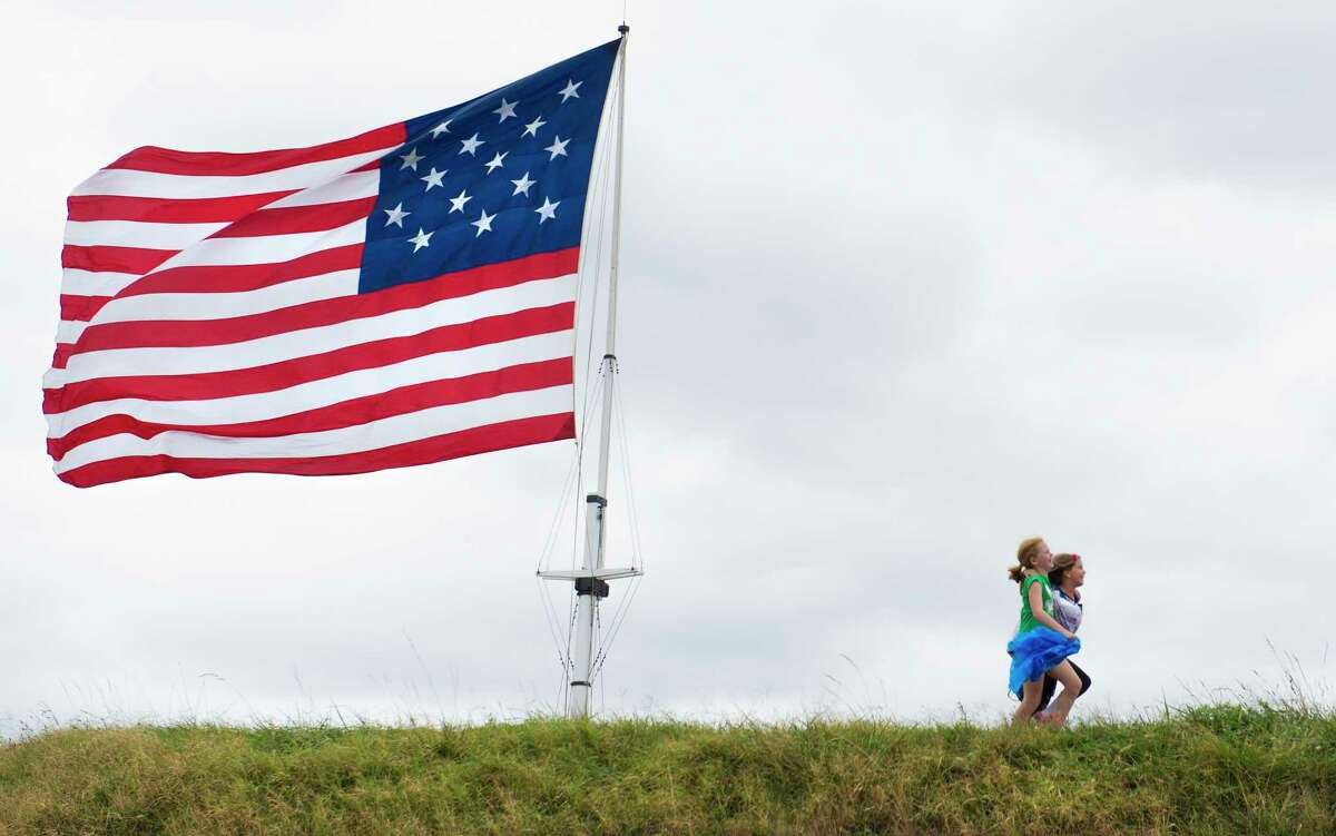 Children play under a reproduction of the 15-star, 15-stripe flag that flew over Fort McHenry during the War of 1812 in Baltimore.