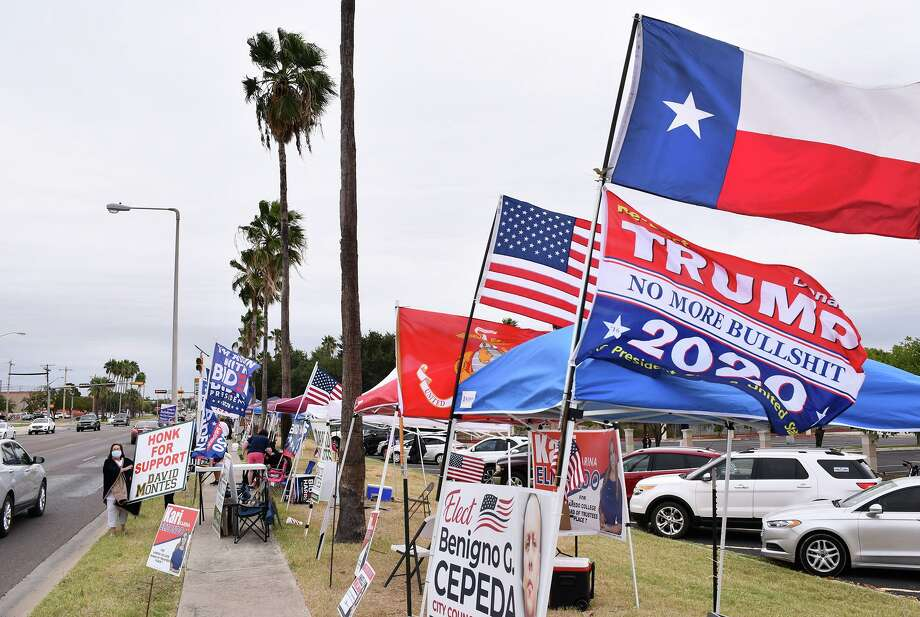 Political supporters are pictured on Friday outside the City of Laredo Fire Station where early voting is taking place. Photo: Cuate Santos /Laredo Morning Times / Laredo Morning Times