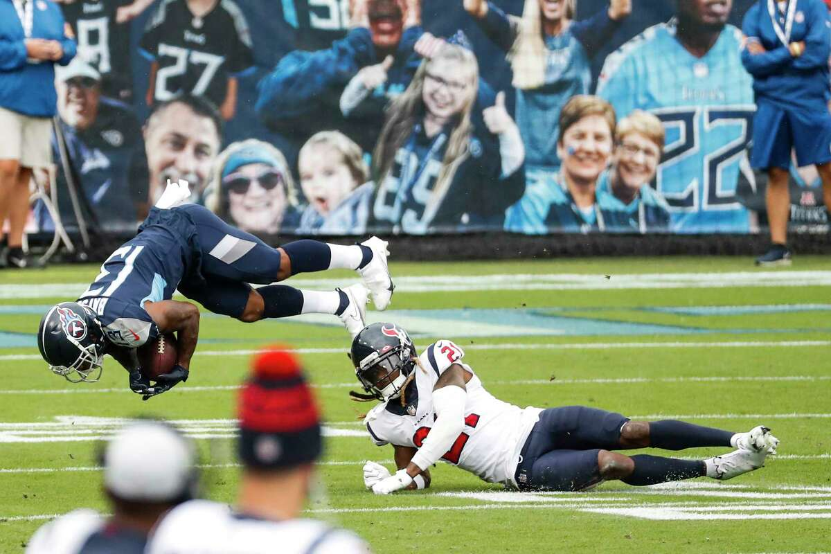 Tennessee Titans wide receiver Cameron Batson (13) is tripped up by Houston Texans cornerback Bradley Roby (21) during the first half of an NFL football game at Nissan Stadium on Sunday, Oct. 18, 2020, in Nashville.