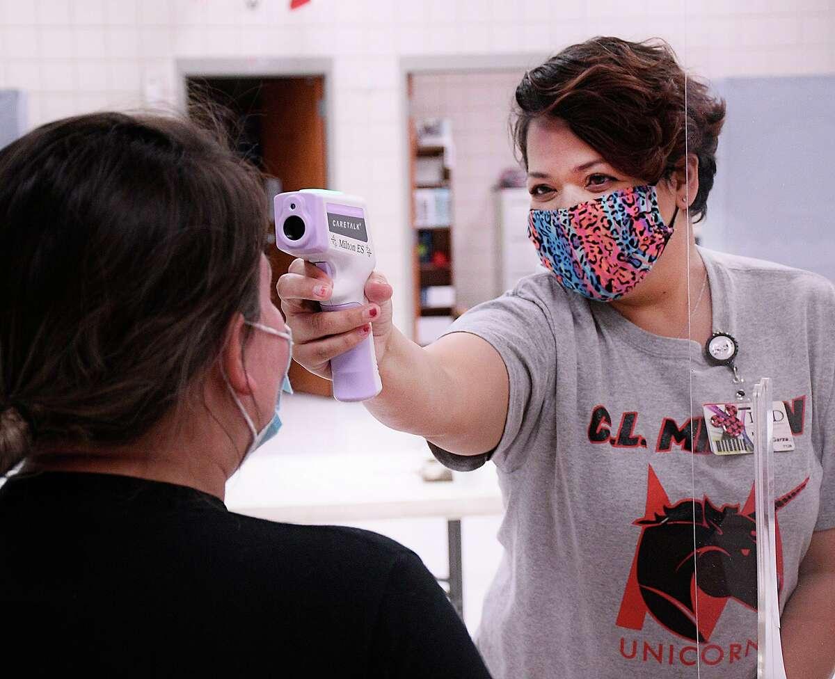 Nurse Assistant Marina De la Garza takes her colleague Aldercy Ortegon's temperature.
