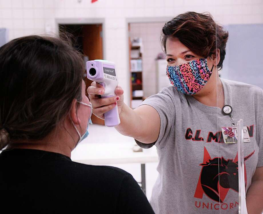 Nurse Assistant Marina De la Garza takes her colleague Aldercy Ortegon's temperature. Photo: Cuate Santos / Laredo Morning Times