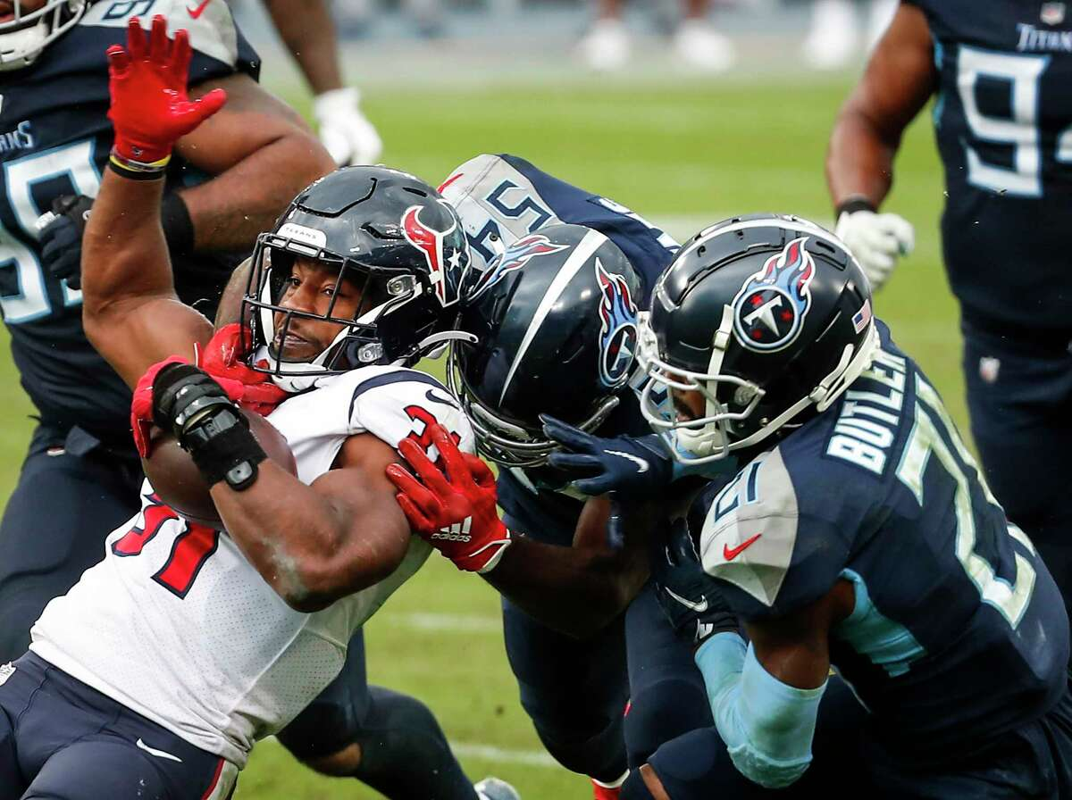 Houston Texans running back David Johnson (31) is stopped by Tennessee Titans inside linebacker Rashaan Evans (54) and cornerback Malcolm Butler (21) during the fourth quarter of an NFL football game at Nissan Stadium on Sunday, Oct. 18, 2020, in Nashville.