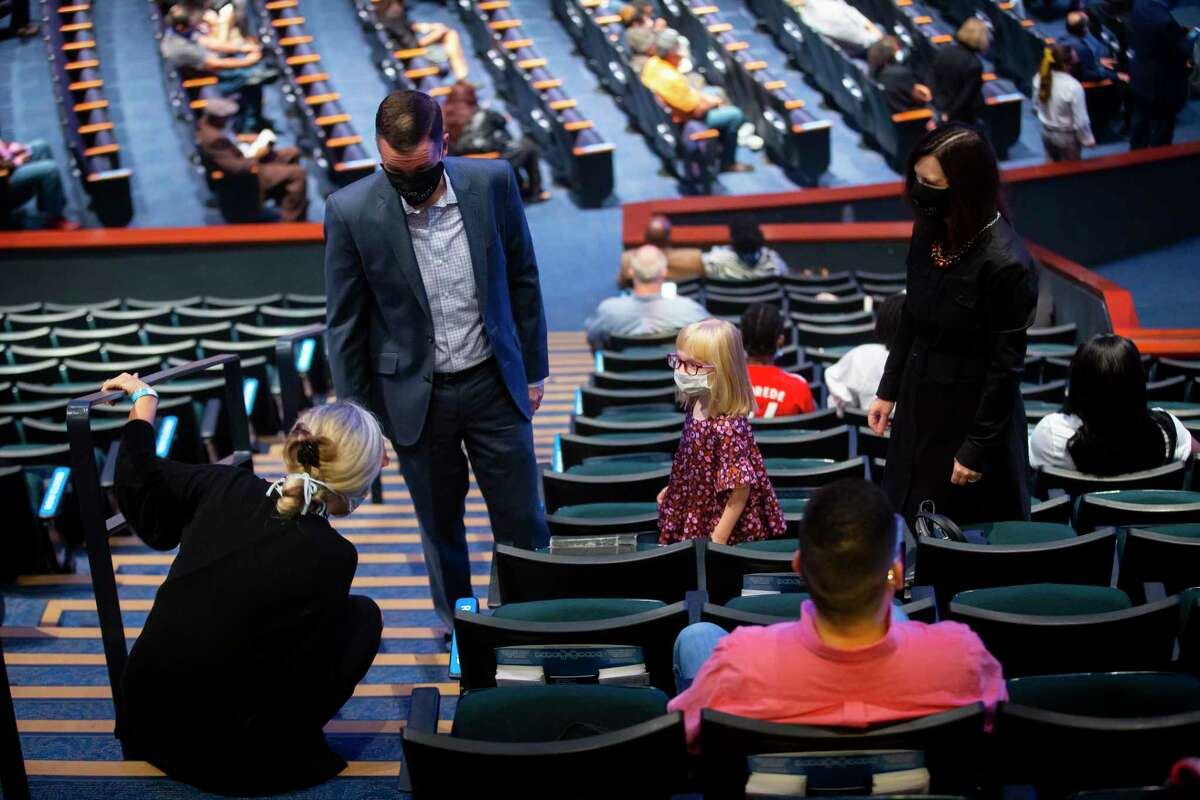 Masked church go-ers greet each other during Lakewood Church's first day of reopening for in-person services on Sunday after being closed since March on Sunday, Oct. 18, 2020.