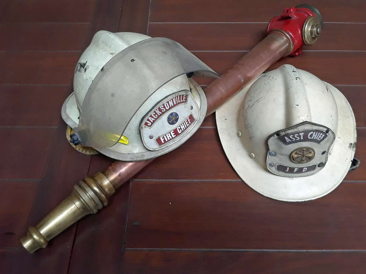 """Campbell family artifacts that were donated to the Jacksonville Area Museum. The helmet on the left belonged to Brad Campbell, Jacksonville Fire Department fire chief from 1997 to 2007. The helmet on the right was originally painted black and belonged to family patriarch Byron """"Humpy"""" Campbell; he gave the helmet to his son, Ron """"Pee Wee"""" Campbell, who later painted it white when he was made an officer. The hose nozzle is from a 1920s-era Jacksonville fire truck."""