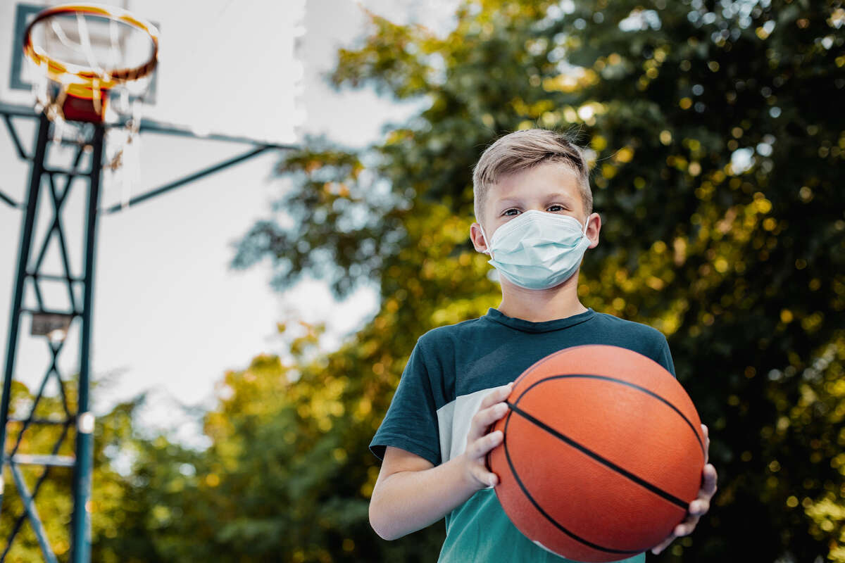 A child holds a basketball while wearing a face mask.