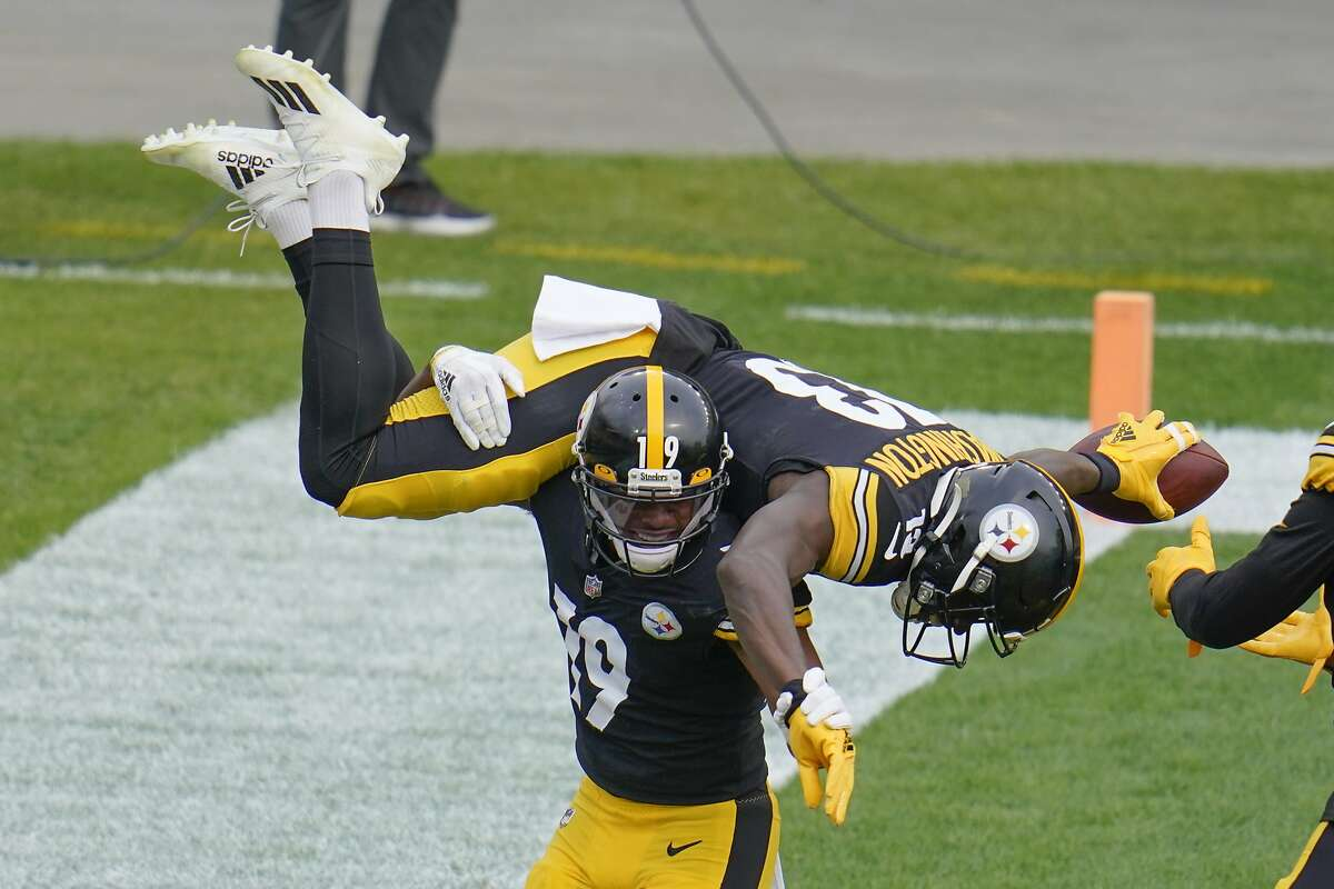 Steelers wide receiver JuJu Smith-Schuster (19) spins fellow wideout James Washington (13) on his shoulders after Washington's first-half TD reception.