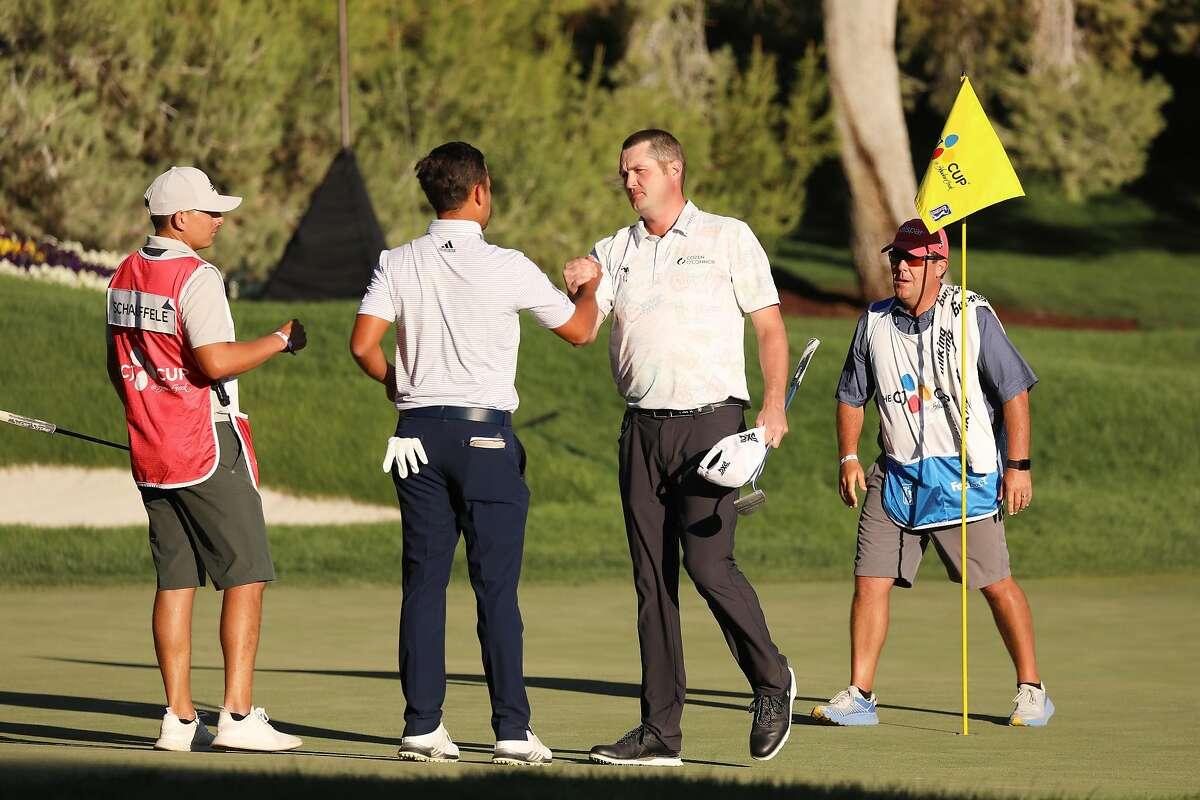Xander Schauffele (left) congratulates first-time PGA winner Jason Kokrak on the 18th green during the final round of The CJ Cup at Shadow Creek in North Las Vegas, Nevada.