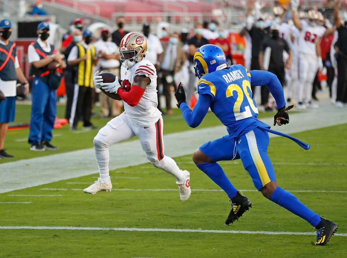 San Francisco 49ers' Deebo Samuel rushes for a 6-yd touchdown in 1st quarter against Los Angeles Rams' Jalen Ramsey during NFL game at Levi's Stadium in Santa Clara, Calif., on Sunday, October 18, 2020.