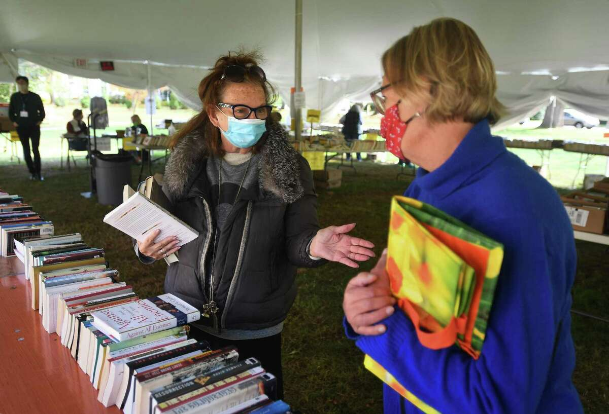 Manya Piels, left, of Westport, and Jane Hickok, of Fairfield, shop for dollar books at the Small Fall Book Sale at the Pequot Library in the Southport section of Fairfield on Sunday.