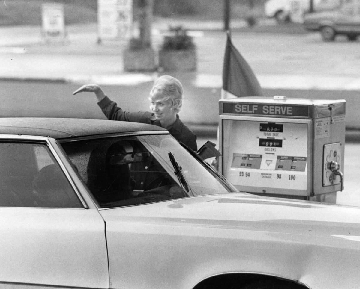 Service station attendant Joy Broker shows customers how to service their own cars at the self-serve island. Stations have cut back on attendant services with the increased use of self-service pumps, April 18, 1973.