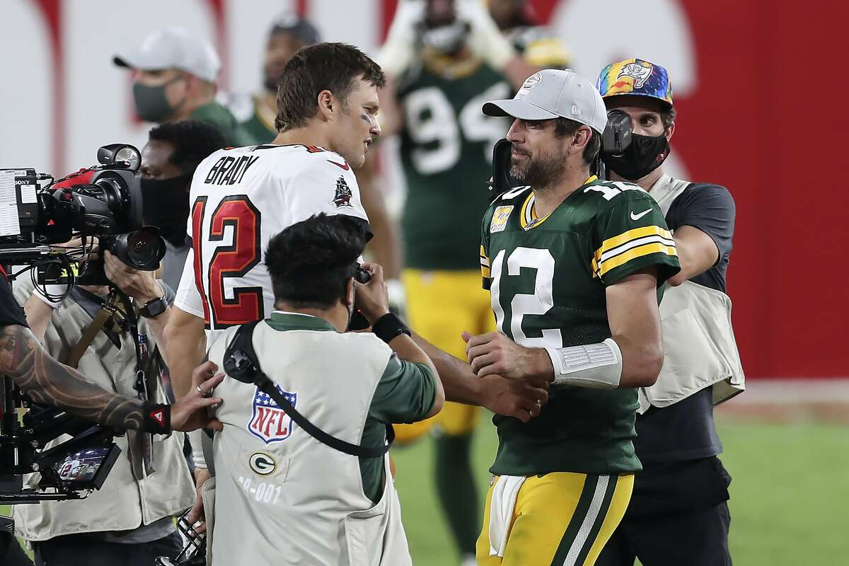 Tom Brady (left, with the Buccaneers) and Aaron Rodgers (Packers) meet for the first time in the postseason Sunday (noon, Fox).