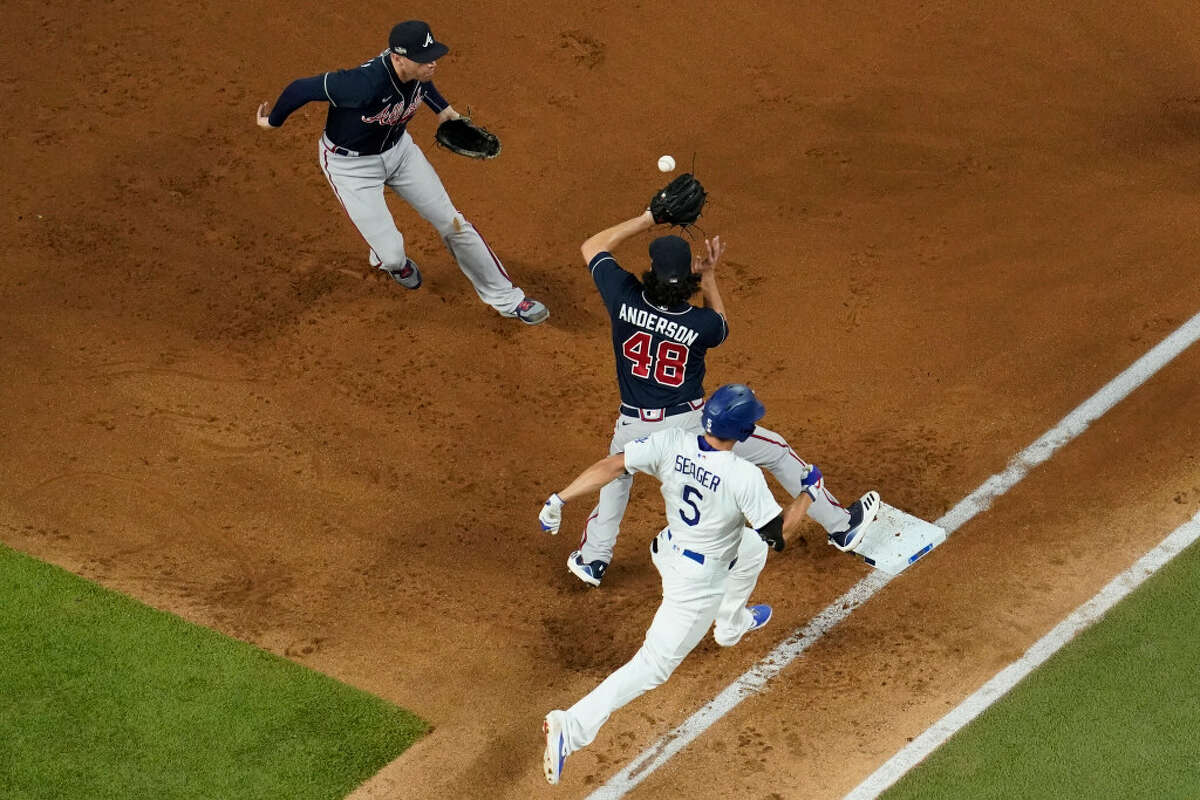 Atlanta Braves first baseman Freddie Freeman and starting pitcher Ian Anderson forces Los Angeles Dodgers' Corey Seager out at first during the first inning in Game 7 of a baseball National League Championship Series Sunday, Oct. 18, 2020, in Arlington, Texas. (AP Photo/David J. Phillip)