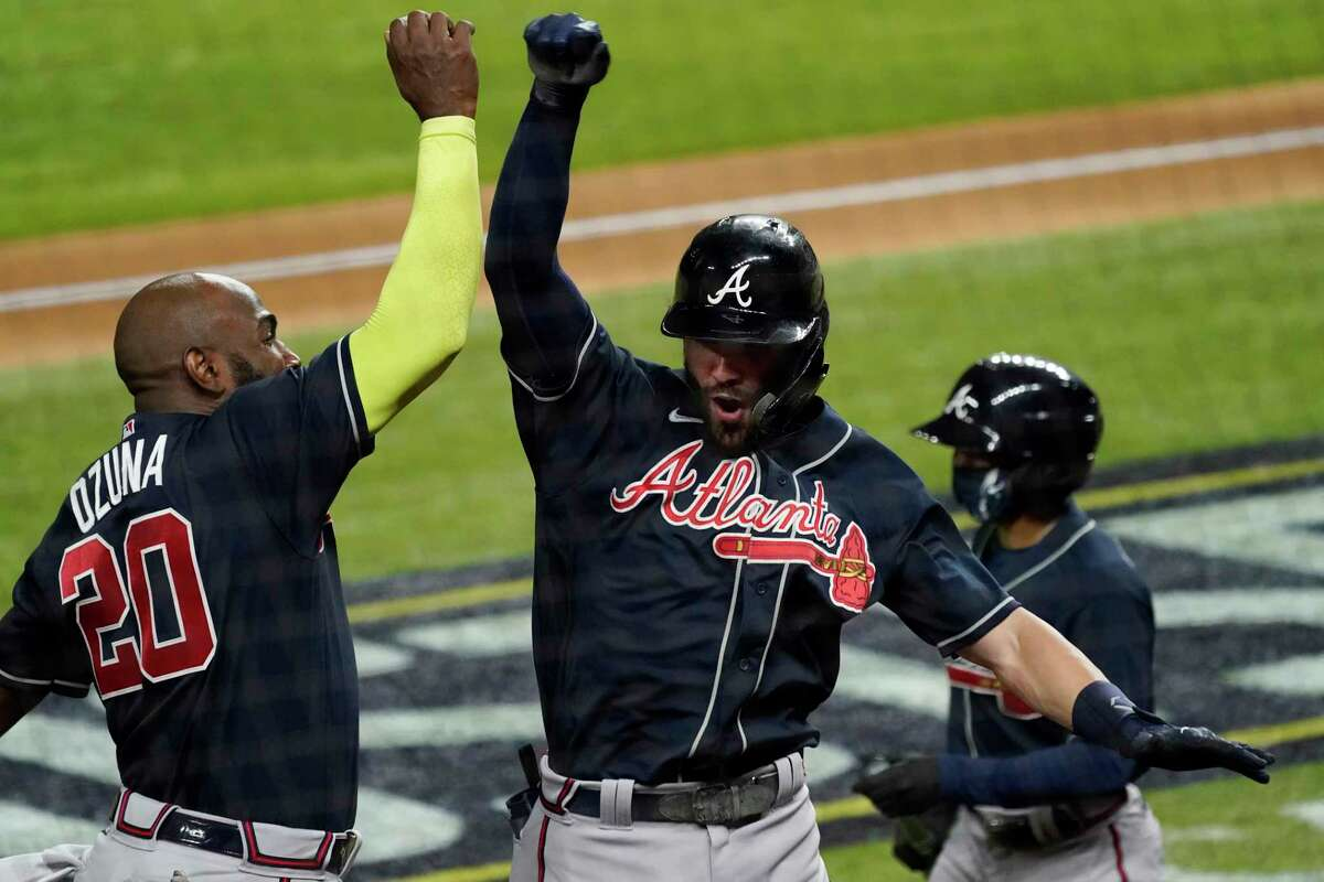 Atlanta Braves' Dansby Swanson celebrates after a home run with Marcell Ozuna against the Los Angeles Dodgers during the second inning in Game 7 of a baseball National League Championship Series Sunday, Oct. 18, 2020, in Arlington, Texas.