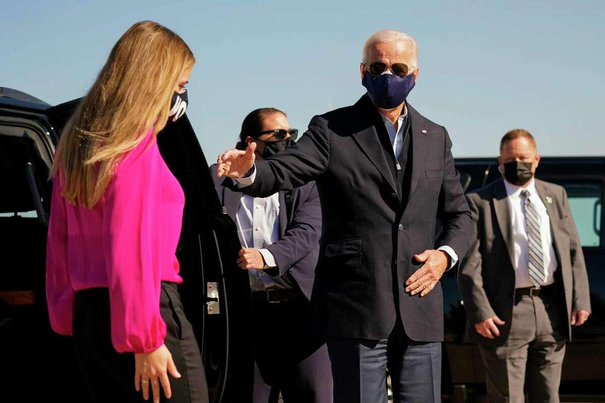 El candidato demócrata a la presidencia, el exvicepresidente Joe Biden y su nieta Finnegan Biden, llegan para abordar el avión de campaña en el aeropuerto de New Castle en New Castle, Delaware, el domingo 18 de octubre de 2020, en ruta a Durham, Carolina del Norte.