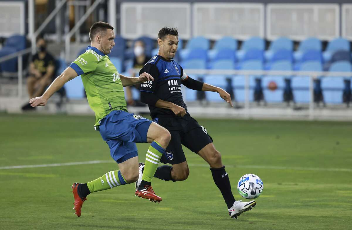 Quakes forward Chris Wondolowski (right) goes against Sounders defender Shane O'Neill at Earthquakes Stadium.