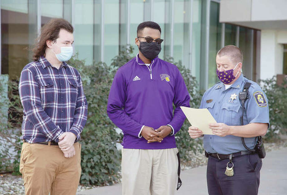 Western Illinois University interim Director Derek Watts presents letters of commendation to Thompson Hall resident assistants Marcus Sweeten and Joshua Smith.